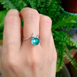 Imagen de anillo con cola de pez en un extremo y en el otro cristal turquesa en dedo