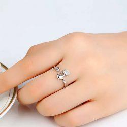 Imagen de anillo con silueta de gato y cola enrosacada en dedo acabada en corazón con incrustaciones brillantes